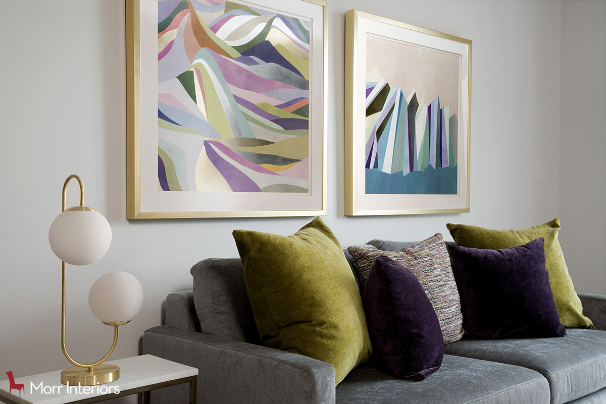 Two golden framed square multicolored artworks hanging above a grey microfiber couch with yellow and purple pillows